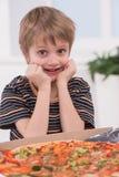 Pequeño muchacho rubio que come en la cocina imagenes de archivo