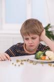 Pequeño muchacho rubio que come en la cocina imagen de archivo libre de regalías