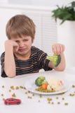 Pequeño muchacho rubio que come en la cocina fotografía de archivo libre de regalías