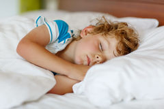 Pequeño muchacho rubio que duerme en su cama Fotos de archivo libres de regalías