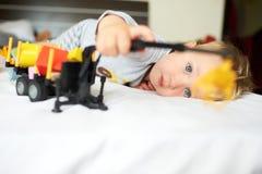 Pequeño muchacho rubio que juega con el coche Foto de archivo libre de regalías