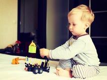 Pequeño muchacho rubio que juega con el coche Imagen de archivo libre de regalías