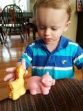 Pequeño muchacho rubio que juega con los animales plásticos del silicón Fotos de archivo