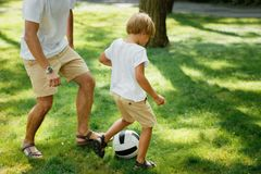 Pequeño muchacho rubio que lleva en la camiseta y los pantalones cortos blancos plaing el footboll con su padre en el césped verd imagenes de archivo