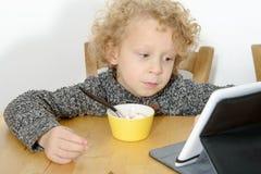 Pequeño muchacho rubio que usa la tableta en casa Foto de archivo