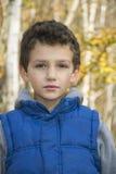 Pequeño muchacho serio en bosque del otoño Imagen de archivo