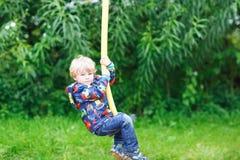 Pequeño muchacho sonriente de tres años que se divierten en el oscilación Imagen de archivo libre de regalías