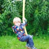 Pequeño muchacho sonriente de tres años que se divierten en el oscilación Fotografía de archivo libre de regalías