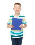 Pequeño muchacho sonriente del estudiante con el libro azul Fotos de archivo