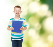 Pequeño muchacho sonriente del estudiante con el libro azul Imágenes de archivo libres de regalías