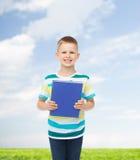 Pequeño muchacho sonriente del estudiante con el libro azul Fotos de archivo libres de regalías