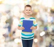 Pequeño muchacho sonriente del estudiante con el libro azul Fotografía de archivo libre de regalías