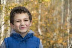 Pequeño muchacho sonriente en bosque del otoño Fotografía de archivo libre de regalías