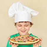Pequeño muchacho sonriente en sombrero de los cocineros con la pizza hecha en casa cocinada Fotos de archivo libres de regalías