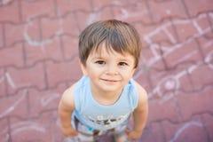 Pequeño muchacho sonriente que mira para arriba Imagen de archivo