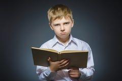 Pequeño muchacho subrayado hermoso con el libro aislado en fondo gris Fotografía de archivo libre de regalías