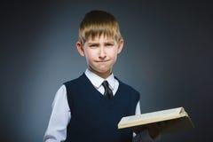 Pequeño muchacho subrayado hermoso con el libro aislado en fondo gris Imagen de archivo