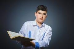 Pequeño muchacho subrayado hermoso con el libro aislado en fondo gris Foto de archivo