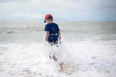Pequeño muchacho valiente que va a nadar en el mar del balanceo solamente Imágenes de archivo libres de regalías