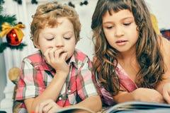 Pequeño muchacho y muchacha caucásicos que mienten en el piso cerca del árbol de navidad y que leen un libro ilustrado fotos de archivo