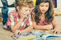 Pequeño muchacho y muchacha rizados caucásicos que mienten en el piso y que leen un libro ilustrado fotografía de archivo