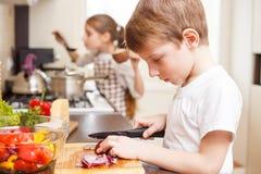 Pequeño muchacho y su hermana que cocinan en la cocina Foto de archivo
