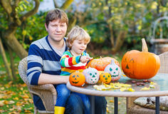 Pequeño niño adorable y su padre que hacen la Jack-o-linterna para Imagen de archivo libre de regalías