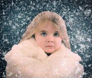 Pequeño niño afuera con nieve que cae del invierno Imagenes de archivo