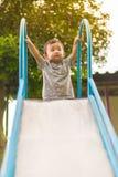 Pequeño niño asiático que juega la diapositiva en el patio Imágenes de archivo libres de regalías