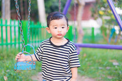 Pequeño niño asiático triste en el patio bajo luz del sol en suma Foto de archivo libre de regalías
