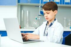 Pequeño niño con el aprendizaje de la clase en laboratorio de la escuela que mecanografía en el ordenador portátil imagen de archivo