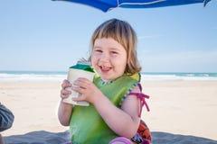 Pequeño niño con el envase de bebidas en manos en la playa Foto de archivo
