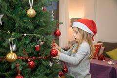 Pequeño niño con el sombrero de Papá Noel que adorna el árbol de navidad Imagen de archivo