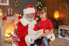 Pequeño niño con historia de la Navidad de la lectura de Santa Claus imágenes de archivo libres de regalías