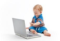 Pequeño niño con la computadora portátil Fotografía de archivo libre de regalías