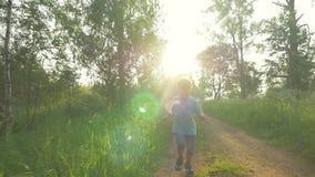 Pequeño niño con la cucharada-red que corre en el país almacen de metraje de vídeo