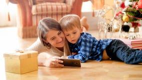 Pequeño niño pequeño con las historietas de observación de la madre en el teléfono el mañana de la Navidad foto de archivo libre de regalías