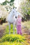 Pequeño niño con un caballo blanco en manzanar Foto de archivo libre de regalías