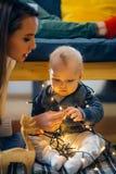 Pequeño niño de la madre y del bebé que juega en el invierno para los días de fiesta de la Navidad Imágenes de archivo libres de regalías