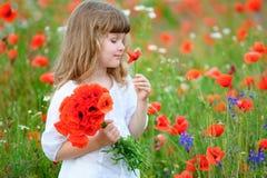 Pequeño niño de la princesa con las flores salvajes rojas Portrai de la muchacha de la belleza fotografía de archivo