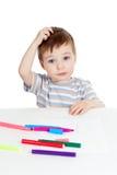 Pequeño niño desconcertado con la pluma del color Imagenes de archivo