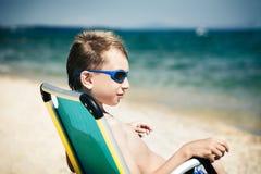 Pequeño niño divertido con las gafas de sol elegantes que se sientan en broncear de la playa Fotografía de archivo libre de regalías