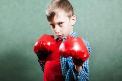 Pequeño niño divertido con los guantes del boxeador que lucha parecer peligroso Imagenes de archivo