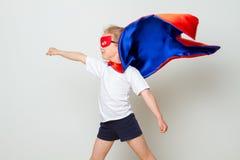 Pequeño niño divertido del superhéroe del poder en un impermeable rojo Concepto del superhéroe fotografía de archivo