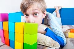 Pequeño niño divertido lindo que miente en un sofá que juega con los cubos coloridos Foto de archivo