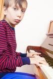 Pequeño niño divertido que juega el piano Imágenes de archivo libres de regalías