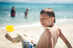 Pequeño niño divertido que se sienta en la sonrisa de la playa arenosa Imagenes de archivo