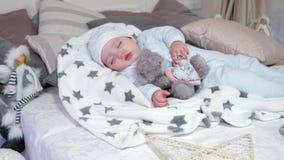 Pequeño niño dormido abrazando un juguete relleno, muchacho que duerme en cama del ` s del padre en una atmósfera acogedora en la metrajes
