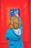 Pequeño niño en cabina de teléfono Imagen de archivo