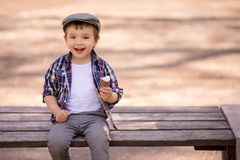 Pequeño niño pequeño en camisa a cuadros y el casquillo que se sientan en banco, comiendo el helado y disfrutando de la vida en d fotos de archivo
